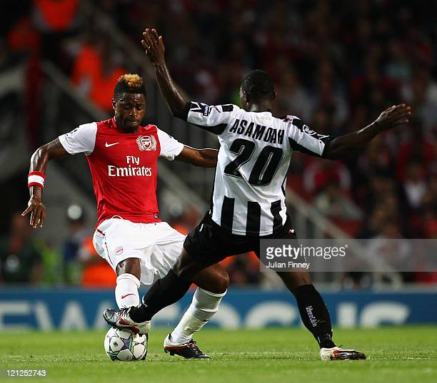 Alex Song of Arsenal and Kwadwo Asamoah of Udinese battle for the ball during the UEFA Champions League playoff first leg match between Arsenal and...