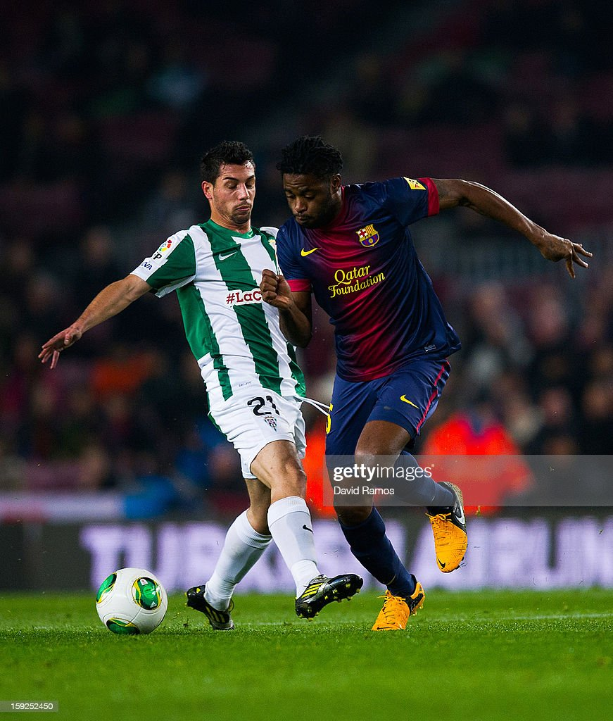 Alex Song of FC Barcelona (R) duels for the ball with Carlos Caballero of Cordoba CF during the Copa del Rey round of sixteen second leg match between FC Barcelona and Cordoba CF at Camp Nou on January 10, 2013 in Barcelona, Spain.