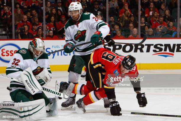Alex Stalock of the Minnesota Wild blocks the puck as Matt Dumba of the Minnesota Wild and Micheal Ferland of the Calgary Flames watch in an NHL game...