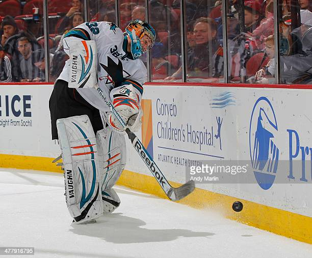 Alex Stalock of the San Jose Sharks controls the puck during game action against the New Jersey Devils at the Prudential Center on March 2 2014 in...