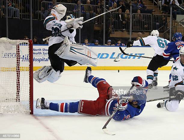 Alex Stalock of the San Jose Sharks jumps to avoid a sliding Rick Nash of the New York Rangers during the second period at Madison Square Garden on...