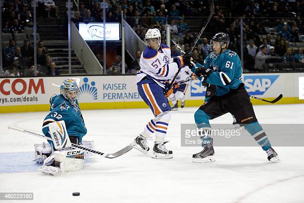 Alex Stalock of the San Jose Sharks makes a save as Justin Braun of the San Jose Sharks and David Perron of the Edmonton Oilers fight for position in...
