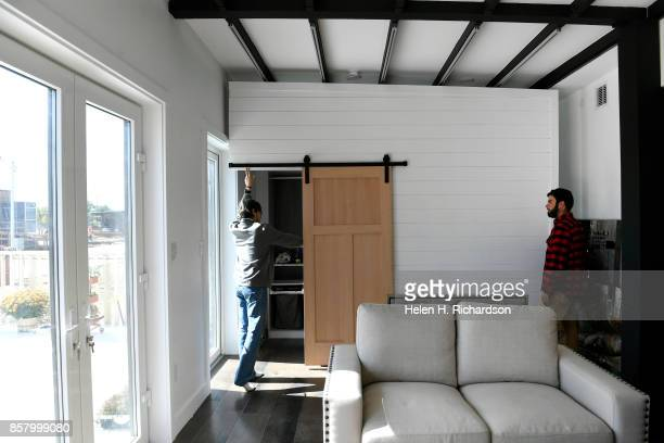 DENVER CO OCTOBER 3 Alex Sundt left and Sam Durkin right of the University of California Berkeley move a wall inside their house to make more space...