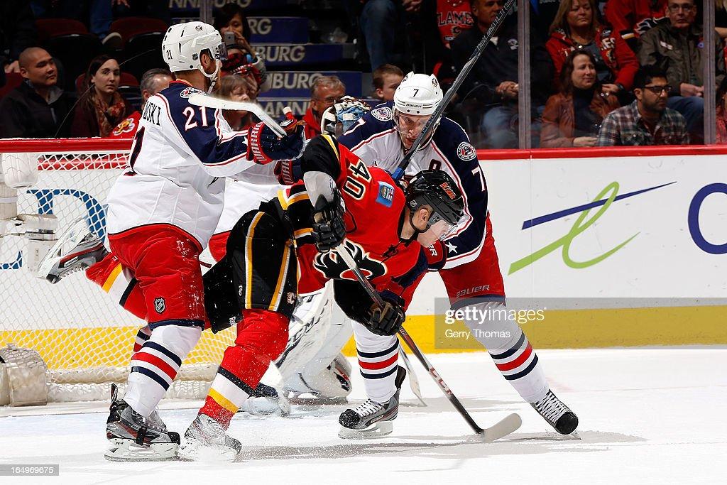 <a gi-track='captionPersonalityLinkClicked' href=/galleries/search?phrase=Alex+Tanguay&family=editorial&specificpeople=203231 ng-click='$event.stopPropagation()'>Alex Tanguay</a> #40 of the Calgary Flames is checked by <a gi-track='captionPersonalityLinkClicked' href=/galleries/search?phrase=James+Wisniewski&family=editorial&specificpeople=688111 ng-click='$event.stopPropagation()'>James Wisniewski</a> #21 and Jack Johnson #7 of the Columbus Blue Jackets on March 29, 2013 at the Scotiabank Saddledome in Calgary, Alberta, Canada.