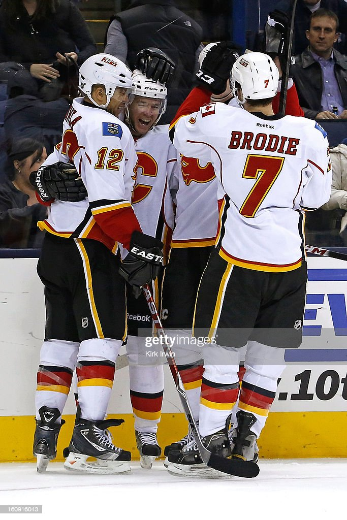 Alex Tanguay #40 of the Calgary Flames is congratulated by his teammates after scoring the game winning goal during the overtime period against the Columbus Blue Jackets on February 7, 2013 at Nationwide Arena in Columbus, Ohio. Calgary defeated Columbus 4-3 in overtime.