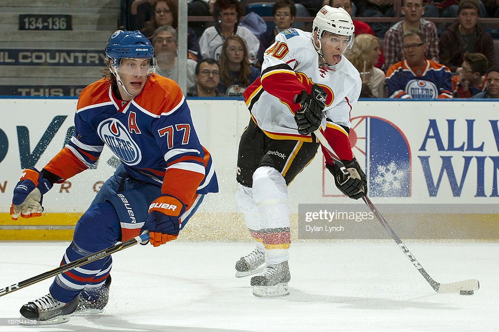 Alex Tanguay #40 of the Calgary Flames makes a pass while Tom Gilbert #77 of the Edmonton Oilers defends at Rexall Place on January 1, 2011 in Edmonton, Alberta, Canada.