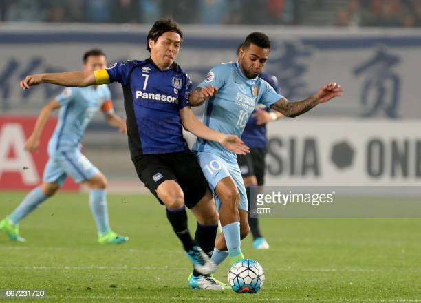 Alex Teixeira of Jiangsu FC fights for the ball with Yasuhito Endo of Japan's Gamba Osaka during their AFC Champions League group stage football...