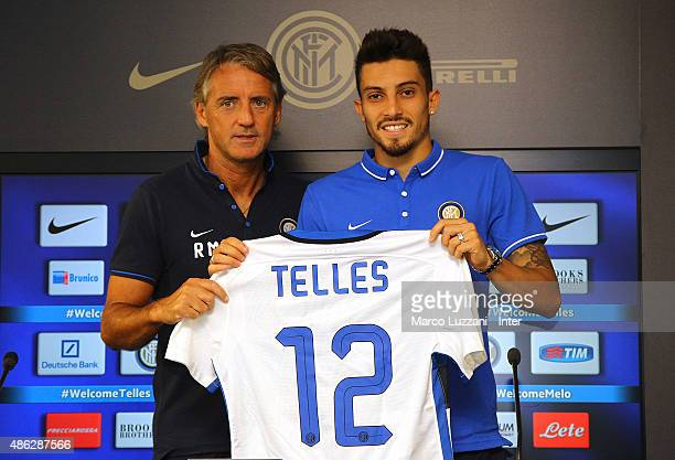 Alex Telles new signing for FC Internazionale Milano pose with the club shirt with FC Internazionale Milano coach Roberto Mancini during a press...