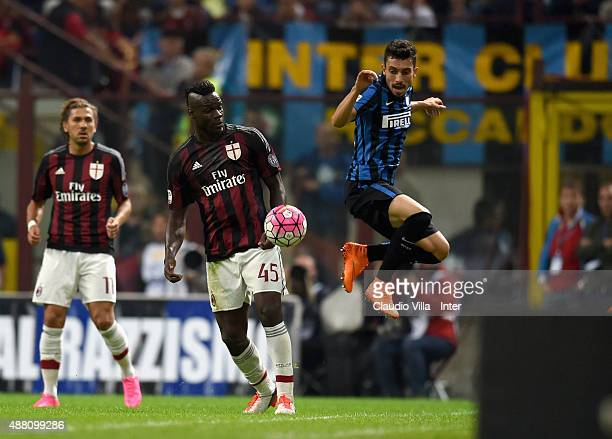 Alex Telles of FC Internazionale and Mario Balotelliof AC Milan compete for the ball during the Serie A match between FC Internazionale Milano and AC...