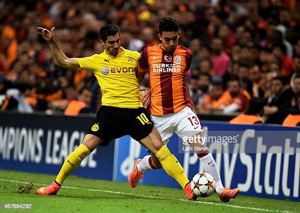 Alex Telles of Galatasaray is tackled by Henrikh Mkhitaryan of Borussia Dortmund during UEFA Champions League Group D match between Galatasaray and...