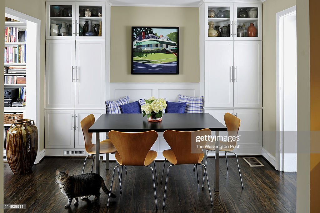 Alex the cat wanders by the banquette in the dining room of McNeill and Noyes's Arlington home