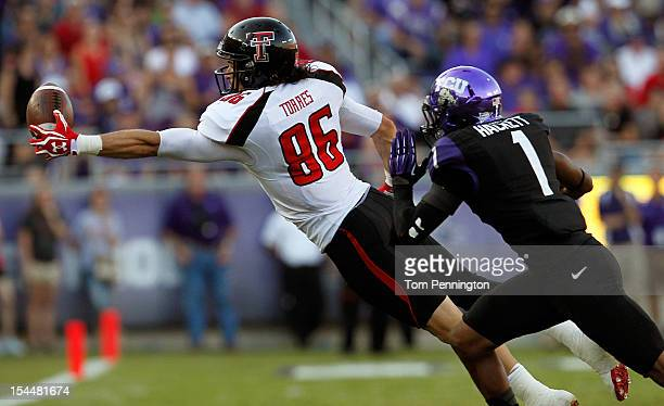 Alex Torres of the Texas Tech Red Raiders pull in a pass for a first down against Chris Hackett of the TCU Horned Frogs at Amon G Carter Stadium on...