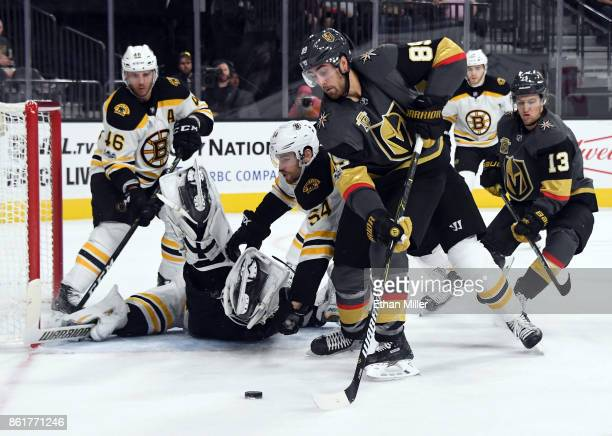 Alex Tuch of the Vegas Golden Knights prepares to pass against Adam McQuaid of the Boston Bruins as Tuukka Rask of the Bruins falls down in the...
