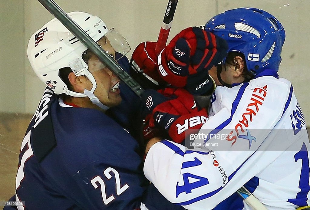 Alex Tuch #22 of USA Blue and Juho Lammikko #14 of Team Finland get their gloves up during the third period in the 2014 USA Hockey Junior Evaluation Camp at the Lake Placid Olympic Center on August 3, 2014 in Lake Placid, New York. USA Blue defeated Team Finland 2-1.