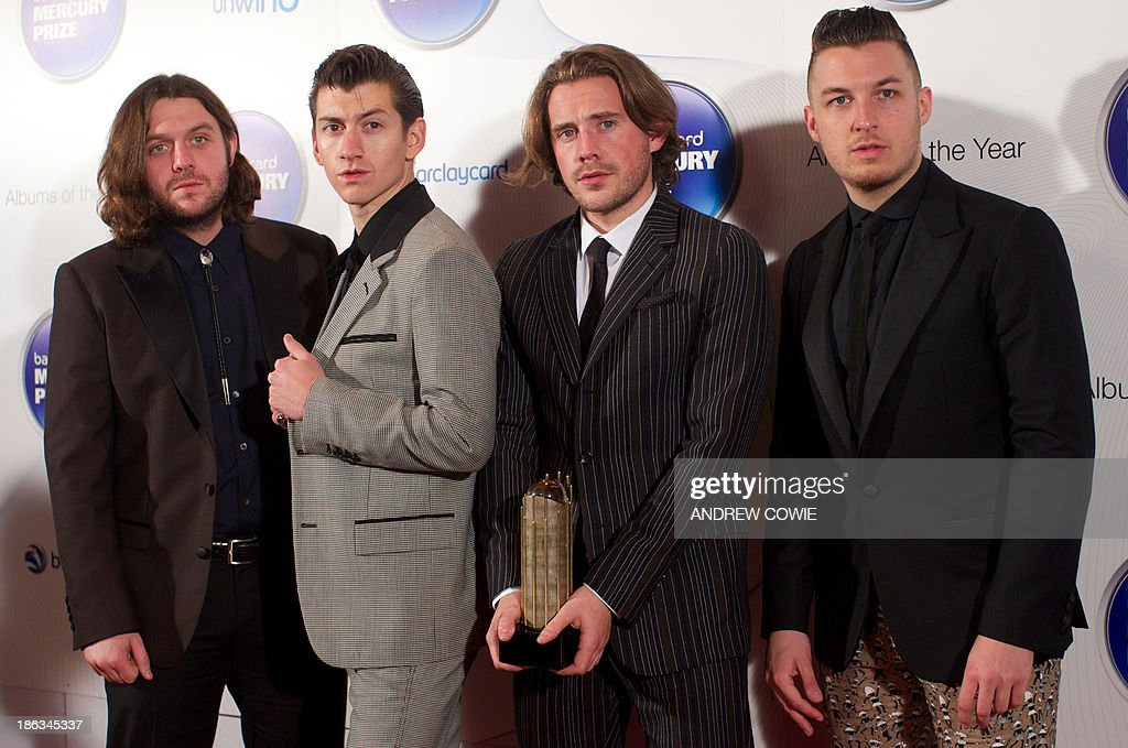 Alex Turner, Jamie Cook, Nick O'Malley and Matt Helders of British indie rock band Arctic Monkeys pose with their Albums of the Year trophy at the 2013 Mercury Prize awards ceremony in central London on October 30, 2011. The Mercury Prize seeks to promote the best of UK and Irish music and the artists that produce it. This is done primarily through the celebration of the 12 Albums of the Year. The12 shortlisted artists receive a specially commissioned bronze Albums of the Year trophy. AFP PHOTO / ANDREW COWIE