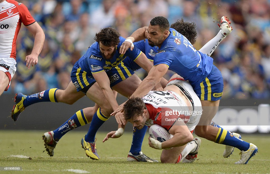 Alex Walmsley of St Helens is tackled by Stefan Ratchford and Ryan Atkins of Warrington Wolves during the Super League match between Warrington Wolves and St Helens at Etihad Stadium on May 18, 2014 in Manchester, England.