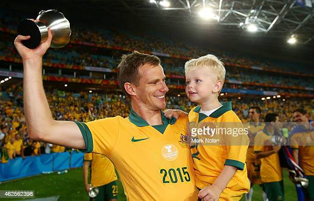 Alex Wilkinson of Australia carries his son on the victory lap after the 2015 Asian Cup final match between Korea Republic and the Australian...