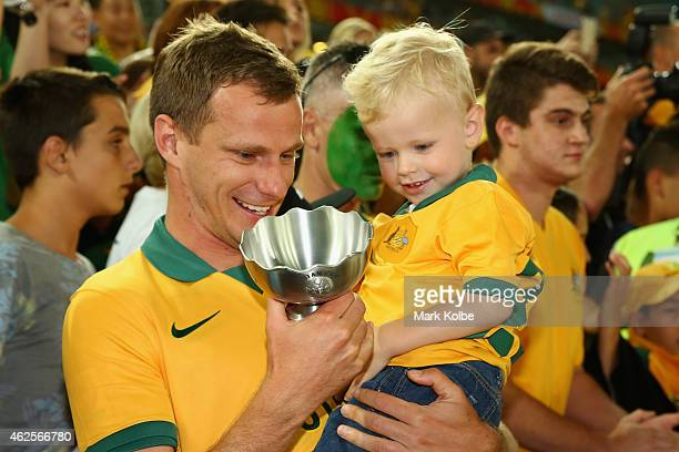 Alex Wilkinson of Australia show his trophy to his son Luca as he clebrates victory during the 2015 Asian Cup final match between Korea Republic and...