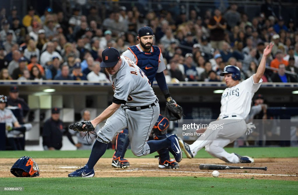 Alex Wilson #30 of the Detroit Tigers tries to field a bunt as Hunter Renfroe #10 of the San Diego Padres scores during the eighth inning of a baseball game at PETCO Park on June 24, 2017 in San Diego, California.