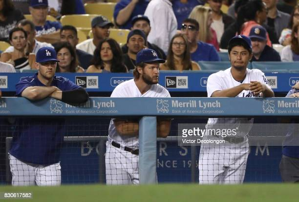 Alex Wood Clayton Kershaw and Yu Darvish of the Los Angeles Dodgers look on from the dugout with the Dodgers down 43 to the San Diego Padres during...