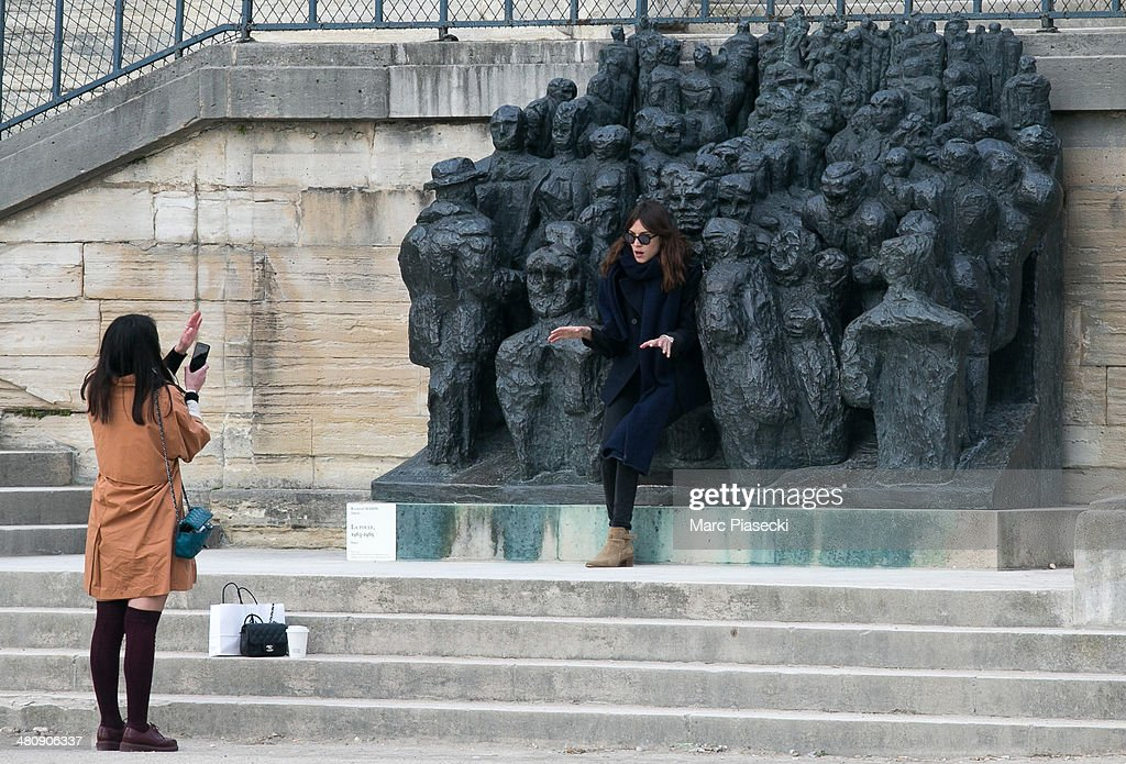 Alexa Chung's friend takes a picture of her in the 'Jardins des Tuileries' on March 27, 2014 in Paris, France.