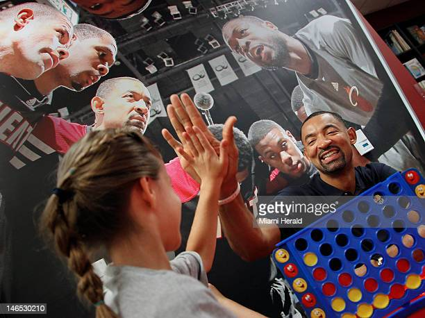 Alexa Garcia gives a 'high five' to Miami Heat player Juwan Howard right while she played 'Connect Four' with the NBA star at the official opening of...
