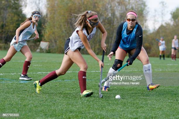 Alexa Koenig center carries the ball as Kelsey Williams moves in during a Freeport High School field hockey practice