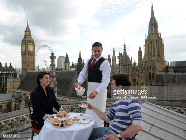 Alexa Mardon and Sean McConaghy enjoy tea served by waiter Chris Riddy on the roof of Westminster Abbey during a photocall commissioned by Visit...