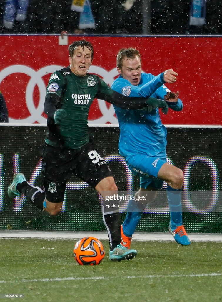 Alexander Anyukov of FC Zenit St. Petersburg (R) and Sergei Petrov of FC Krasnodar vie for the ball during the Russian Football League Championship match between FC Zenit St. Petersburg and FC Krasnodar at the Petrovsky stadium on December 6, 2014 in St. Petersburg, Russia.