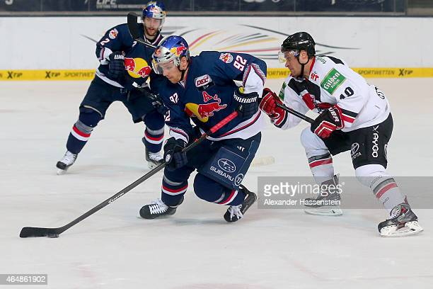 Alexander Barta of Muenchen is challenge by James Johnson of Koeln during the DEL Ice Hockey match between EHC Red Bull Muenchen and Koelner Haie at...