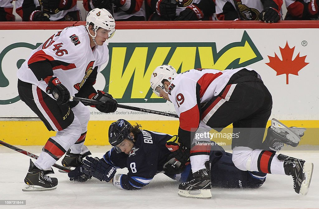 Alexander Burmistrov #8 of the Winnipeg Jets falls to the ice between Patrick Wiercioch #46 and <a gi-track='captionPersonalityLinkClicked' href=/galleries/search?phrase=Jason+Spezza&family=editorial&specificpeople=202023 ng-click='$event.stopPropagation()'>Jason Spezza</a> #19 of the Ottawa Senators during third-period action on January 19, 2013 at the MTS Centre in Winnipeg, Manitoba, Canada.
