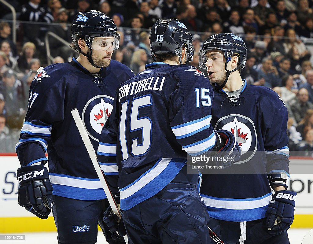 Alexander Burmistrov #8 of the Winnipeg Jets gives instructions to teammates Eric Tangradi #27 and Mike Santorelli #15 during a third period stoppage against the Buffalo Sabres at the MTS Centre on April 9, 2013 in Winnipeg, Manitoba, Canada.