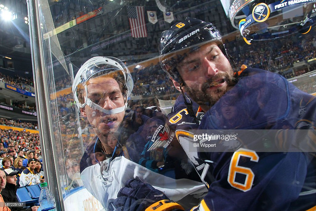 Alexander Burmistrov #8 of the Winnipeg Jets has his helmet dislodged while being checked by Mike Weber #6 of the Buffalo Sabres on April 22, 2013 at the First Niagara Center in Buffalo, New York.