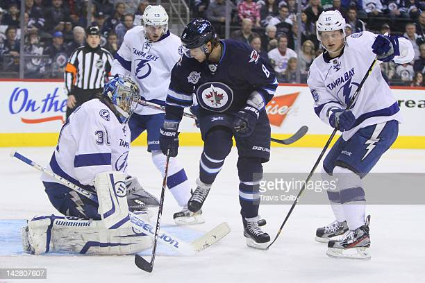 Alexander Burmistrov of the Winnipeg Jets positions himself between goaltender Dwayne Roloson Brendan Mikkelson and Brian Lee of the Tampa Bay...