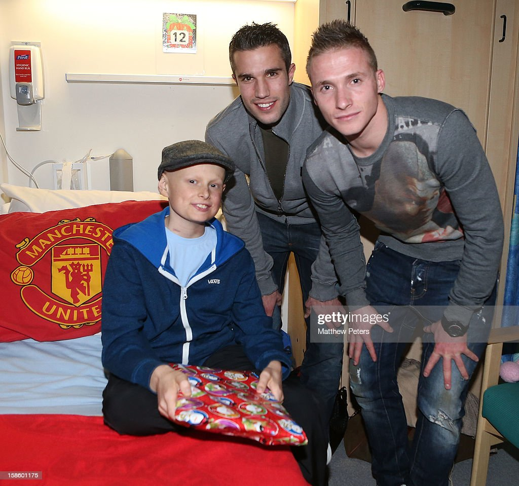 Alexander Buttner and Robin van Persie of Manchester United give presents to Morgan Helliwell, 13, from Milnrow, as part of the Manchester United Foundation annual Christmas hospital visits at the Royal Manchester Children's Hospital on December 20, 2012 in Manchester, England.
