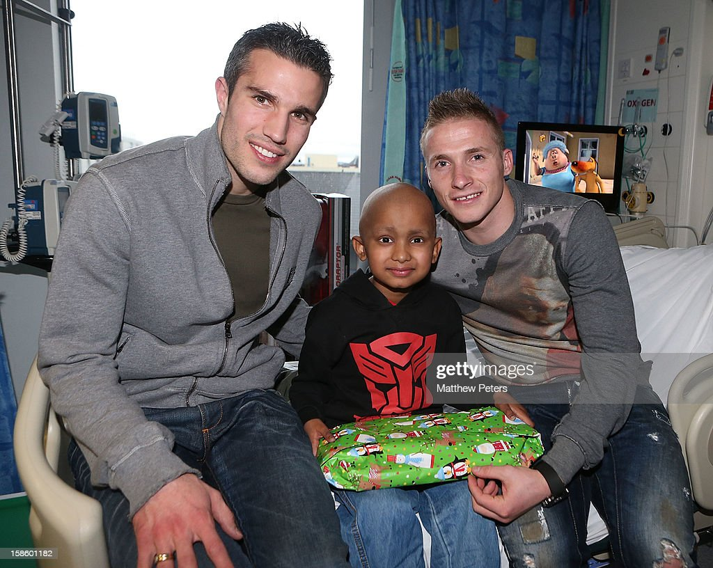 Alexander Buttner and Robin van Persie of Manchester United give presents to Aiden Tinu, 6, from Blackpool, as part of the Manchester United Foundation annual Christmas hospital visits at the Royal Manchester Children's Hospital on December 20, 2012 in Manchester, England.