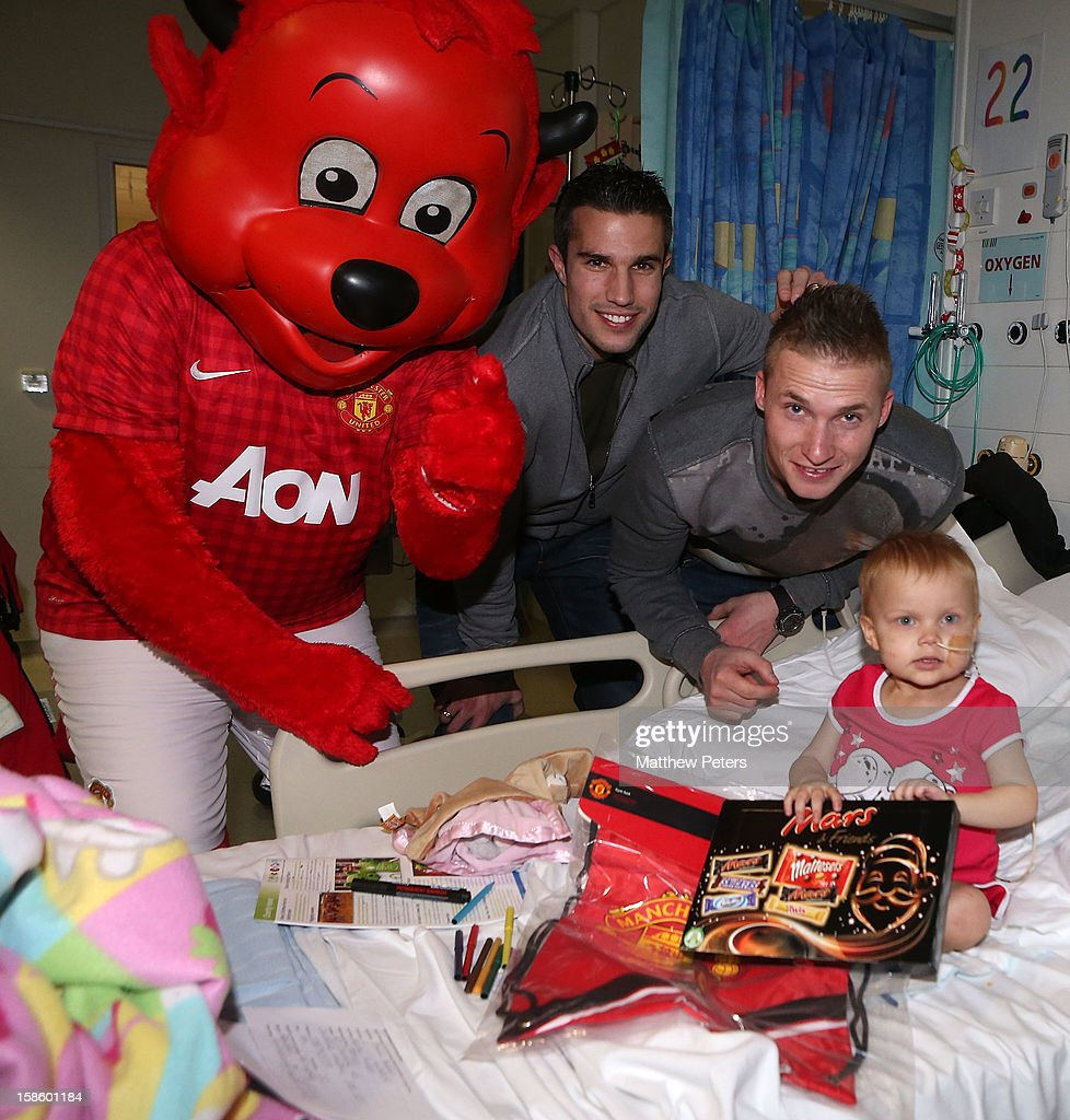 Alexander Buttner and Robin van Persie of Manchester United give presents to Emilie Auston, 2, from Cheadle Hulme, as part of the Manchester United Foundation annual Christmas hospital visits at the Royal Manchester Children's Hospital on December 20, 2012 in Manchester, England.