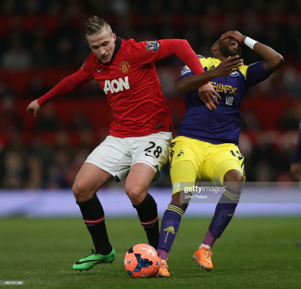 Alexander Buttner of Manchester United in action with Dwight Tiendalli of Swansea City during the FA Cup Third Round match between Manchester United and Swansea City at Old Trafford on January 5, 2014 in Manchester, England.