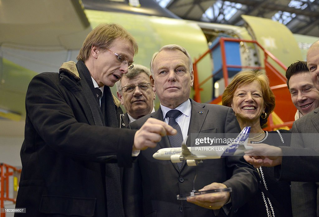 Alexander Dahm, chief of the final assembly line of the Airbus A320, holding a miniature of the A320 airplane explains to French Prime Minister Jean-Marc Ayrault (C) during a visit of the final A320 airplane assembly line on February 22, 2013 in Hamburg. Ayrault is on a visit to Hamburg participating on the traditional Matthiae-Mahl.