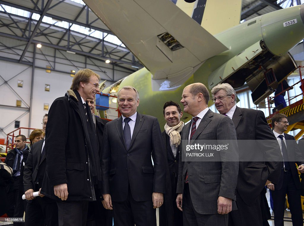 Alexander Dahm (L), chief of the final assembly line of the Airbus A320 family, French Prime Minister Jean-Marc Ayrault (C), and Hamburg's First Mayor Olaf Scholz stand in front of a A320 airplane on February 22, 2013 in Hamburg. Ayrault is on a visit to Hamburg participating on the traditional Matthiae-Mahl. AFP PHOTO / PATRICK LUX