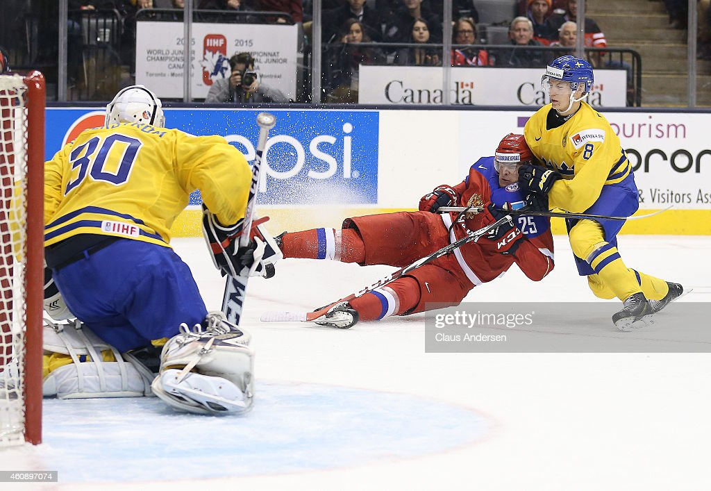 Alexander Dergachyov of Team Russia is brought down by Gustav Forsling of Team Sweden before he could get a shot away in a 2015 IIHF World Junior...