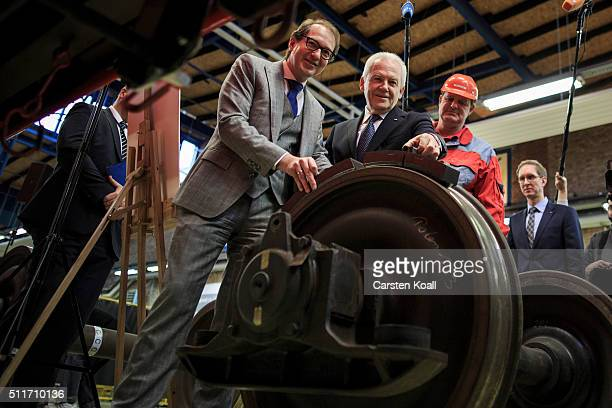 Alexander Dobrindt and Ruediger Grube CEO of Deutsche Bahn hold new technology brake pads in front of a DB AG goods wagon during a workshop where the...