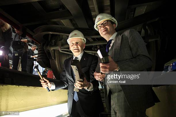Alexander Dobrindt and Ruediger Grube CEO of Deutsche Bahn hold new and old technology brake pads under a DB AG goods wagon during a workshop where...