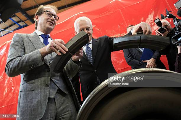 Alexander Dobrindt and Ruediger Grube CEO of Deutsche Bahn hold new technology pads at a DB AG workshop during which freight cars are fitted with new...