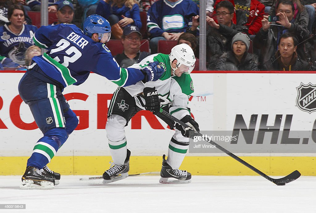 Alexander Edler #23 checks Vernon Fiddler #38 of the Dallas Stars during their NHL game at Rogers Arena on November 17, 2013 in Vancouver, British Columbia, Canada. Dallas won 2-1.