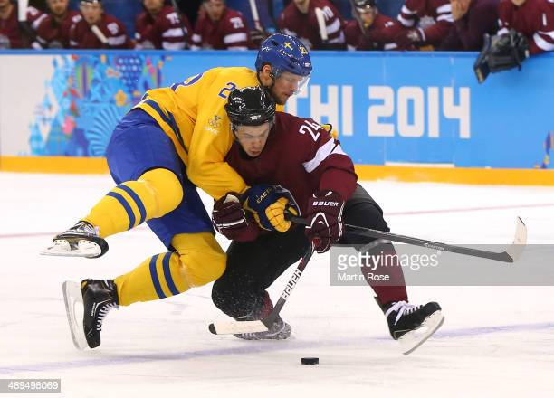 Alexander Edler of Sweden and Mikelis Redlihs of Latvia go for a loose puck in the first period during the Men's Ice Hockey Preliminary Round Group C...