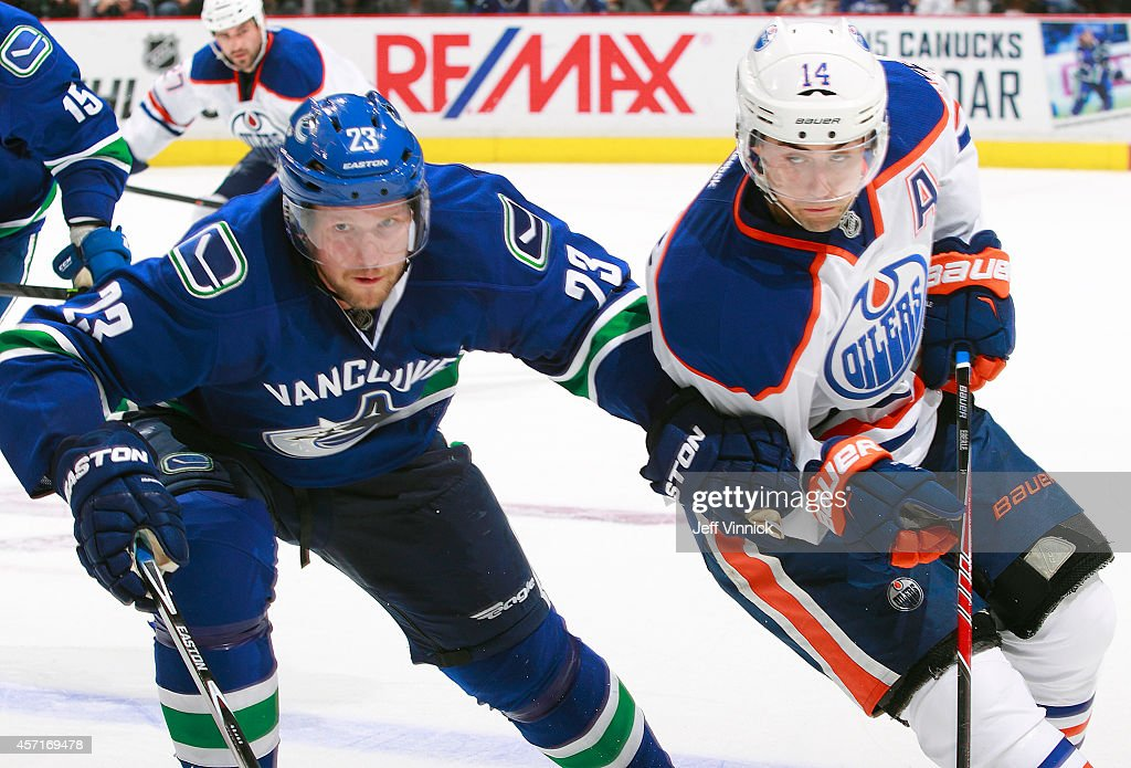 Alexander Edler #23 of the Vancouver Canucks and Jordan Eberle #14 of the Edmonton Oilers skate up ice during their NHL game at Rogers Arena October 11, 2014 in Vancouver, British Columbia, Canada. Vancouver won 5-4 in a shootout.