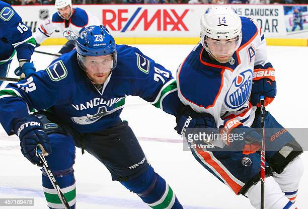Alexander Edler of the Vancouver Canucks and Jordan Eberle of the Edmonton Oilers skate up ice during their NHL game at Rogers Arena October 11 2014...
