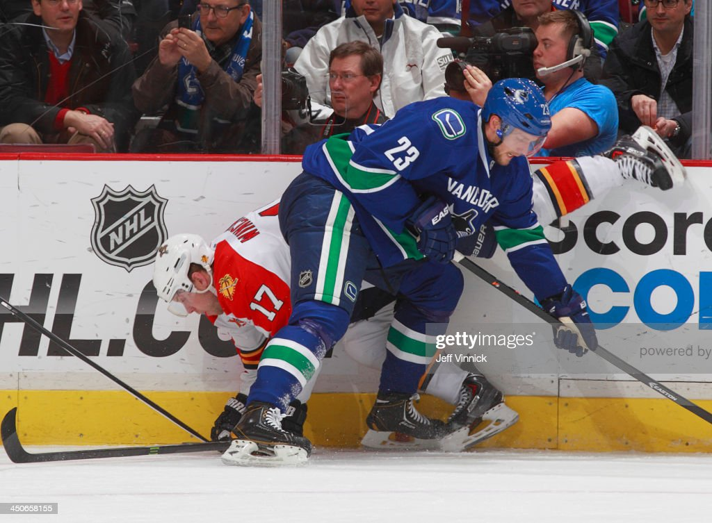 Alexander Edler #23 of the Vancouver Canucks checks Jesse Winchester #17 of the Florida Panthers during their NHL game at Rogers Arena on November 19, 2013 in Vancouver, British Columbia, Canada.