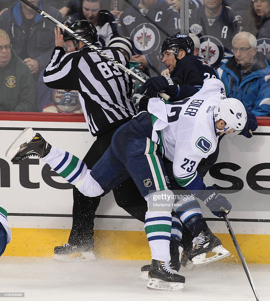 <a gi-track='captionPersonalityLinkClicked' href=/galleries/search?phrase=Alexander+Edler&family=editorial&specificpeople=882987 ng-click='$event.stopPropagation()'>Alexander Edler</a> #23 of the Vancouver Canucks collides with <a gi-track='captionPersonalityLinkClicked' href=/galleries/search?phrase=Blake+Wheeler&family=editorial&specificpeople=716703 ng-click='$event.stopPropagation()'>Blake Wheeler</a> #26 of the Winnipeg Jets and linesman Matt MacPherson #83 in third-period action in an NHL game at the MTS Centre on March 12, 2014 in Winnipeg, Manitoba, Canada.